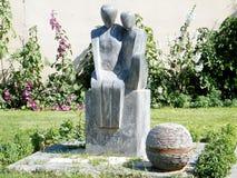 Neve Monosson-beeldhouwwerk op een achtergrond van stokrozen 2011 Stock Afbeeldingen