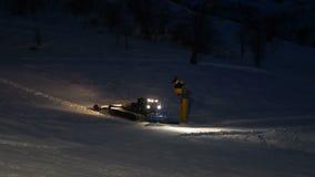 Neve muoventesi dello spazzaneve di gatto delle nevi nella notte con i fari sopra stock footage