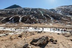 Neve preta do witn da montanha e abaixo com os turistas na terra com grama marrom, neve e a lagoa congelada no inverno no ponto z Imagem de Stock