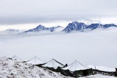 Neve que acampa na parte superior de um pico Foto de Stock Royalty Free