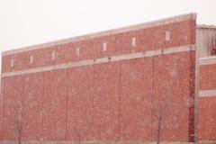 Neve que cai na construção de tijolo vermelho imagem de stock