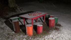 Neve que cai nas maçãs colocadas na tabela de madeira vermelha na área rural no inverno filme