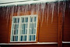 Neve, sincelos e represa do gelo na janela do telhado e da calha Fotografia de Stock