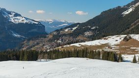 Neve sulla collina e villaggio nell'inverno Immagini Stock