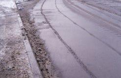 Neve sulla strada con le tracce dell'automobile fondo, stagionale fotografia stock
