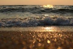 Nevel van de overzeese golf en het gouden zand bij zonsondergang royalty-vrije stock foto