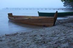 Nevelige ochtend op het meer Twee boten bij de kust dichtbij oude verlaten pijler Stock Afbeelding