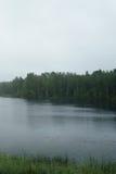 Nevelige ochtend op Skandinavisch meer met regenrimpelingen op water royalty-vrije stock afbeeldingen