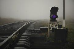 Nevelige spoorwegsporen en donkerblauwe spoorweglantaarn royalty-vrije stock foto