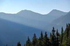 nevelige zonsopgang in Slowaakse Tatra-bergen met lichte stegen in F stock afbeelding