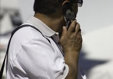 Never Without It. A man dressed in white stays connected with the cell phone wherever he goes Royalty Free Stock Images