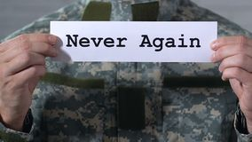 Never again written on paper in hands of male soldier, world peace concept. Stock footage stock video