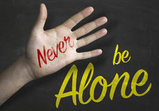 Never Be Alone message on blackboard Stock Photography