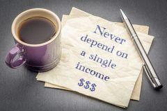 Never depend on a single income. Handwriting on napkin with a cup of coffee Stock Photos