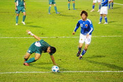 Never give up. East Asian Games, Football: Japan VS Macau, Macau\'s player was fell down but try to stand up to catch the ball Stock Photography