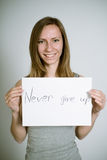 Never give up. Portrait of a real young woman on a light background in a gray shirt with the sign in her hands. Shallow depth of field. Focus on the eyelashes Royalty Free Stock Photos