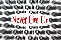 Never Give Up Text. Closeup detail of black and white words with red word of never giving up to inspire hard work and commitment Stock Photography
