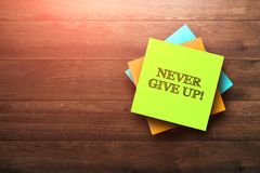 Free Never Give Up , The Phrase Is Written On Multi-colored Stickers, On A Brown Wooden Background. Environment Concept, Strategy, Plan Royalty Free Stock Image - 158232976