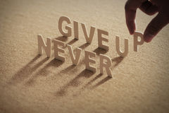 NEVER GIVE UP wood word on compressed board Stock Images