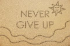 Never give up word with smiling sun and wave on sand Stock Images