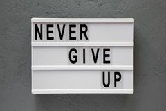 `Never give up` words on modern board over concrete background. Flat lay, from above, overhead. Closeup stock photos