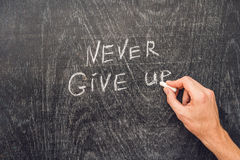 Never give up words written on the chalkboard Royalty Free Stock Photos