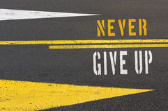Never Give Up written on asphalt road. Royalty Free Stock Image