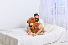 Never grow up concept. Guy on happy face hugs giant teddy bear. Macho with beard and mustache cuddling with plush toy. Man sits on bed and hugs big toy, white Stock Photography