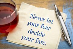 Never let your fear decide fate. Never let your fear decide your fate - inspiraitonal handwriting on a napkin with a cup of tea stock image
