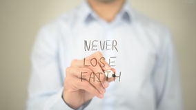 Never Lose Faith , Man writing on transparent screen stock image