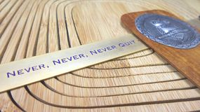 Never quit sign and owl tin sign on wooden background Royalty Free Stock Photography