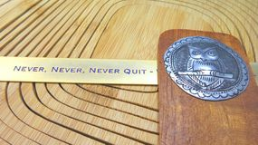Never quit sign and owl tin sign on wooden background Royalty Free Stock Images