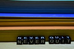 Never quit written on wooden blocks. Education and business concept royalty free stock images