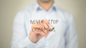 Never Stop Dreaming,  Man writing on transparent screen Royalty Free Stock Photo