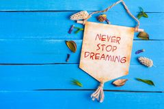 Never stop dreaming text on Paper Scroll. Never stop dreaming text on Canvas Paper Scroll with dried flower around and blue wooden background royalty free stock photos