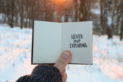 Never stop exploring. Inspirational and motivational quotes. . Book and text. Never stop exploring. Inspirational and motivational quotes. Hand holding a book Royalty Free Stock Photos