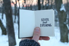 Never stop exploring. Motivational quotes. Book with text and snowy winter park. royalty free stock photos