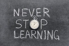 Never stop learning. Phrase handwritten on chalkboard with vintage precise stopwatch used instead of O Stock Photos