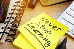 Never stop learning written on a stick. Lifelong learning concept. Never stop learning written on a memo stick. Lifelong learning concept stock image