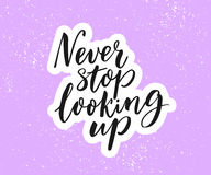 Never stop looking up. Inspirational quote, brush calligraphy on purple background. Stock Image