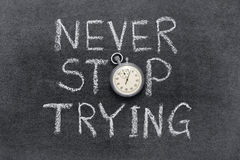 Never stop trying. Phrase handwritten on chalkboard with vintage precise stopwatch used instead of O Royalty Free Stock Images