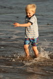 Never too cold for fun. Small boy is having fun on the irish beach in the sunset Royalty Free Stock Photography