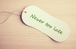 Never too late. Label is on the wooden desk background Royalty Free Stock Photos