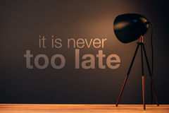It is never too late motivational quote message. On office wall behind desk illuminated by the lamp Stock Image