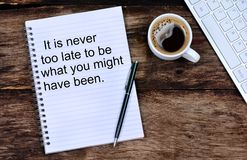 It is never too late to be what you might have been. Inspirational quote. On notepad royalty free stock photo