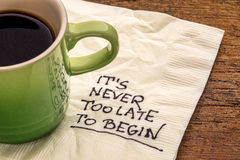 It is never too late to begin. Motivational reminder on a napkin with a cup of coffee royalty free stock images