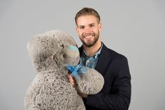 It is never too late to have happy adulthood. Man hols big teddy bear, grey background. Birthday gift concept. Teddy. Bear pleasant surprise. Guy happy hold stock photo