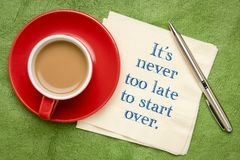 It is never too late to start over. Handwriting on a napkin with a cup of coffee against colorful textured paper royalty free stock photo