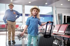 Cute child and old man are waiting for flight. Never travel alone. Portrait of little girl is standing at airport and holding suitcase with toy while looking at Royalty Free Stock Photography