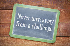 Never turn away from a challenge blackboard sign. Against rustic barn wood table Royalty Free Stock Photo